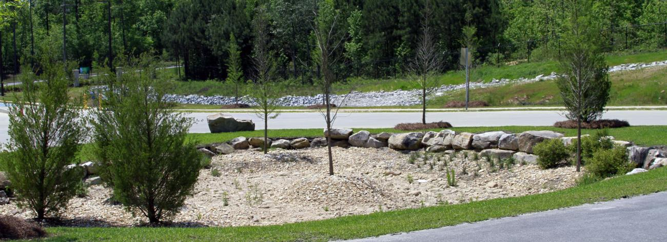 Storm-water is contained in an attractive detention area landscaped with boulders and native plant material.